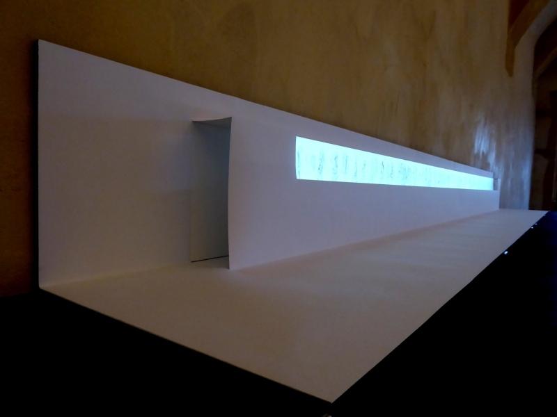 L'animation PASSANT [entre deux portes] est projetée sur un écran de papier Dimensions : 7,5 x 230 cm